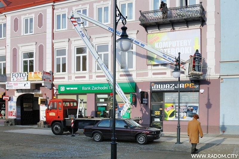Radom. Wieszanie reklamy na kamienicy przy ul. Żeromskiego 9.